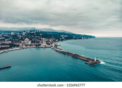 Aerial view of Yalta embankment from drone, old Lighthouse on pier, sea coast landscape and city buildings on mountains, beautiful winter panorama of European resort, Crimea.