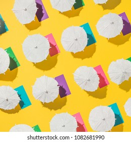 Aerial view of yellow sand beach with white sun umbrellas and colorful beach towels. Minimal summer pattern.