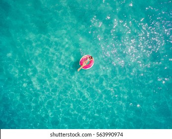 Aerial view of young brunette woman floating on the inflatable big donut in the transparent turquoise sea. Top view of slim lady relaxing on her holidays in Thailand, Phuket, Andaman sea.