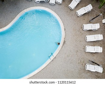 Aerial view of a young girl in black swimsuit, blue swimming pool and white sunbeds