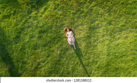 Aerial view. Young girl lying and resting on lawn on sunny day in park on grass. Above view. Woman on grass in meadow. Top view