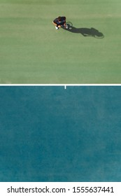 Aerial view of young male tennis player standing on hard court. Professional tennis player on hardcourt.