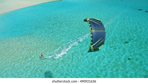 Aerial view young man kitesurfing in tropical blue ocean, extreme sport