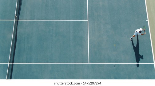 Aerial view of young tennis player playing on hard court. Professional tennis player hitting a backhand on court.