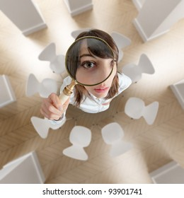 Aerial view of a young woman looking above through a magnifying glass