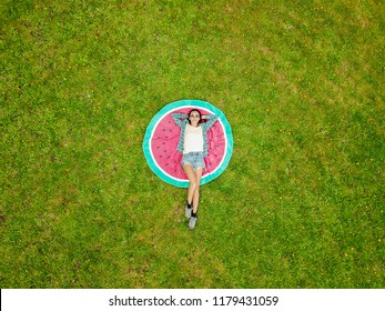 Aerial view of young woman lying on her back on the round towel and green grass. Beach towel looks like a watermelon from the top.