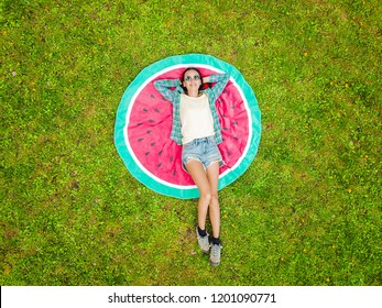 Aerial view of young woman lying on her back on the round towel and green grass. Beach towel looks like a watermelon.