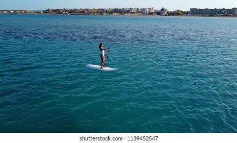Aerial view. Young Woman on Paddle Board. SUP