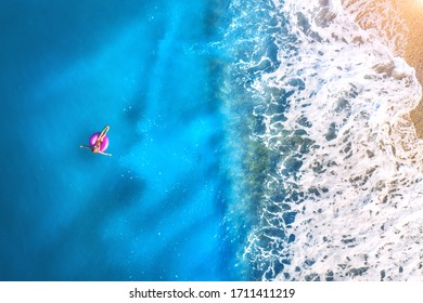 Aerial view of a young woman swimming with the donut swim ring in the clear blue sea with waves at sunset in summer. Tropical landscape with girl, azure water, sandy beach. View from above. Travel