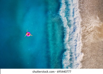 Aerial view of young woman swimming on the pink swim ring in the transparent turquoise sea in Oludeniz,Turkey. Summer seascape with girl, beautiful waves, azure water in sunny day. Top view from drone