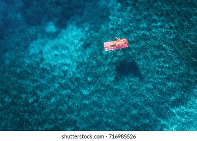 Aerial view of young woman swimming on the pink inflatable mattress floating on transparent turquoise sea in Ichmeler,Turkey. Summer seascape with girl, azure water, air mattress. Top view from drone