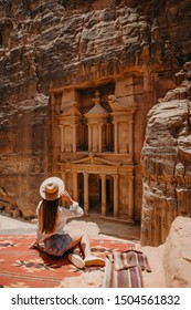Aerial view of young woman tourist sitting on a cliff after reaching the top, Al Khazneh in the ancient city of Petra, Jordan, UNESCO World Heritage Site