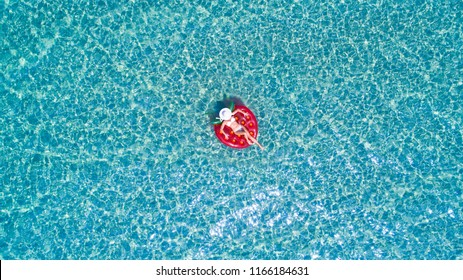 Aerial view of young woman in a white bikini is chilling on a red rubber mattress in the transparent, blue sea.