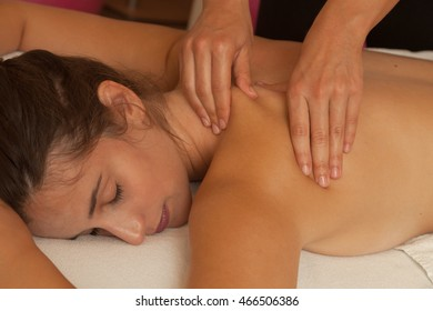 Aerial view of a young woman's body lying on a bed receiving a massage on her back during a physiotherapy session