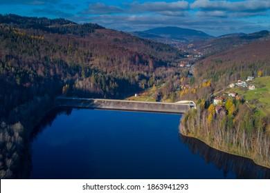 Luftbild von Zapora Wisla Czarne, Wasserdamm in Polen in der Nähe von Wisla, mit großem Akkumulationssee hinter dem Staudamm im Spätherbst.