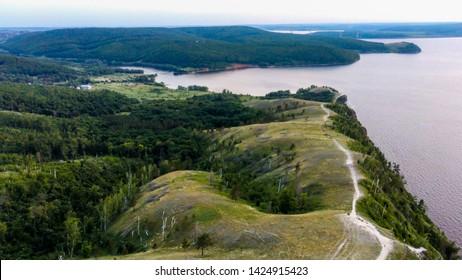 Aerial view of Zhiguli mountains with green trees and Volga river in Samarskaya Luka national park during summer evening, Samara region, Russia