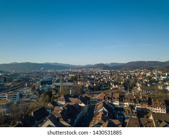 Aerial View Zofingen small city in Switzerland with historic church and old town buildings and Swiss Alps in the backdrop. Concept: architecture, history, tourism, cityscape, medieval town, church