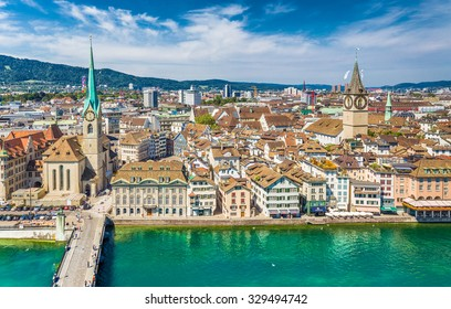 Aerial view of Zurich city center with famous St. Peter Church and river Limmat at Lake Zurich from Grossmunster Church on a sunny day with blue sky and clouds in summer, Canton of Zurich, Switzerland