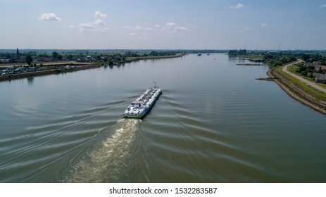 Aerial view:Barge with cargo on the river. River, cargo barge, highway with cars.. Cargo ship on the river