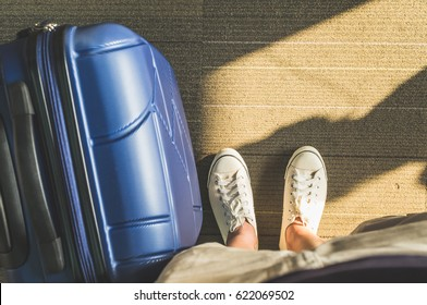 Aerial view,Looking down at white sneakers and travel suitcase with morning sunlight through window at airport terminal,Vacation concept