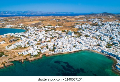 Aerial viewpoint of the city of Naoussa with typical white houses by the sea and low mountains on the horizon, Paros island, Greece
