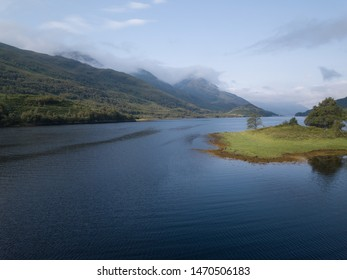 aerial viewpoint of loch leven near glen coe in the fort william area of the highlands of scotland in summer during a morning showing clear blue water and cloudy skies with an island in the foreground