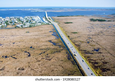 Aerial views of road through the marsh and bridge crossing Manteo to Nags Head with marina