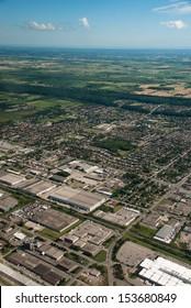 Aerial of warehouses beside residential houses
