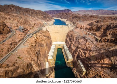 Aerial wide angle view of famous Hoover Dam, a major tourist attraction located on the border between the states of Nevada and Arizona, on a beautiful sunny day with blue sky and clouds in summer, USA