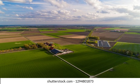Aerial wide angle view of typical Dutch agricultural landscape with green fields in the foreground blue sky with clouds casting shadows on the land tulip fields in the distance, farm houses Holland