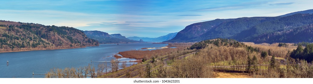 Aerial wide panorama over Rooster Rock State Park with shades of browns and grays and blues looking down the beautiful Columbia River Gorge on a Winter day with blue sky