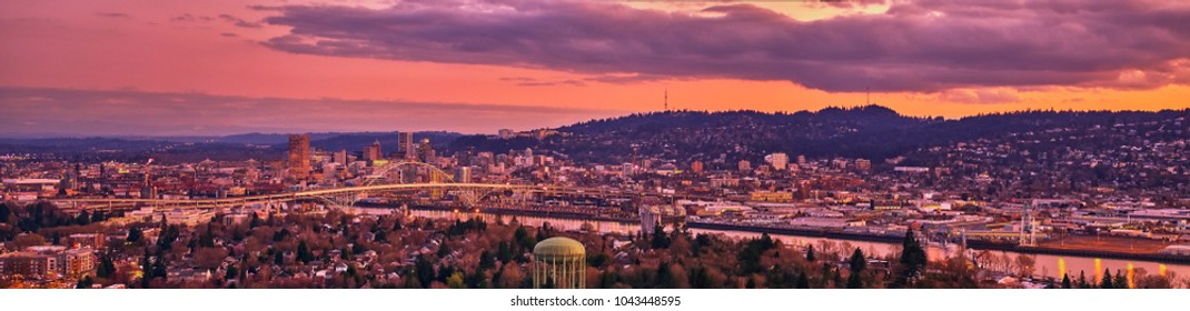 Aerial wide panorama sunset over downtown Portland Oregon showing the waterfront, the Fremont Bridge,  Broadway Bridge, and US Bank Corp Tower on a cold Winters evening showing