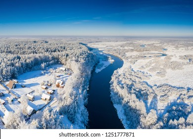 Aerial winter landscape. River with snowy riversides view from above. Belarus winter landscape.