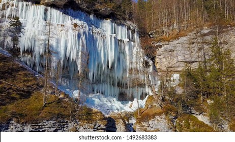 AERIAL Winter river cascade frozen into white sparkling icicles. Stunning frost icicles hanging from rocky mountain cliff on winter day. Early spring sun melting icy waterfall water drops dropping off