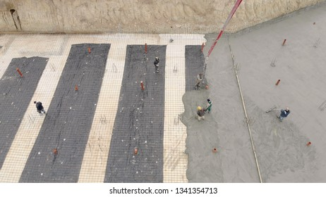 Aerial Workers work on the construction site. The process of pouring concrete foundations of the future home