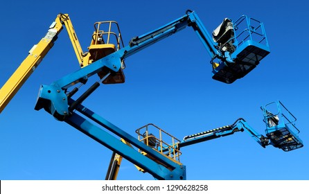 Aerial working platforms of cherry picker against blue sky