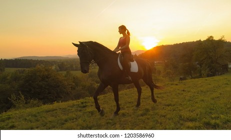 AERIAL: Young Caucasian girl rides her brown horse through the countryside at spectacular sunrise. Picturesque shot of happy young woman and her horse trotting on a beautiful sunny summer evening.
