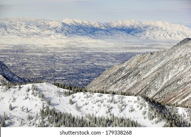 Aerial zoomed view from the top of Snowbird Ski Resort, in Utah looking down over Salt Lake City in winter.