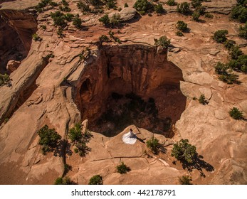 Aerial/Drone Wedding photo of a Bride in her wedding dress on a cliff overlooking a massive sinkhole in the Utah Desert, near Moab.