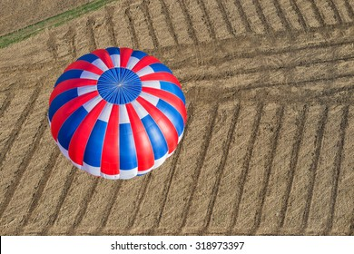 aeriel view of  hot air balloon flying over a stripped field