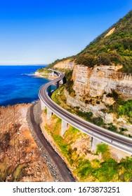 Aerival view over scenic road in Australia - the Grand Pacific Drive with famous Sea Cliff Bridge on a sunny day.