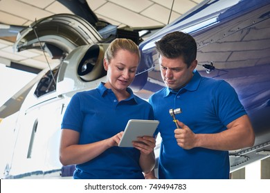Aero Engineer And Apprentice Working On Helicopter In Hangar Looking At Digital Tablet
