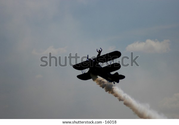 Aerobatic biplane carrying a wingwalker flying into the sky.
