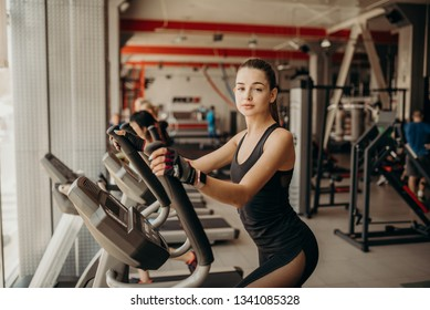 Aerobics cardio training. Sportive woman working out on elliptical machine at gym