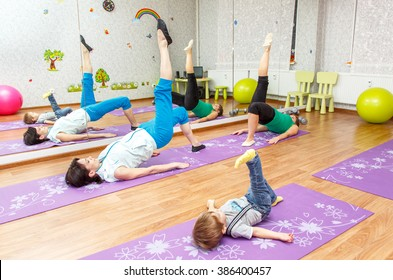 Aerobics pilates. Woman, kid boy and personal instructor at gym