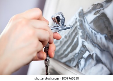 An aerograph unit or paint sprayer in human hand drawing on canvas, close up view