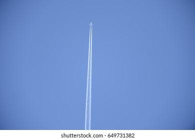 Aeroplane flies through the sky leaving a condensation trail
