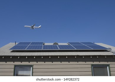 Aeroplane flying over rooftop with solar panels in Los Angeles; California