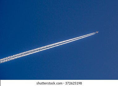 Aeroplane flying through clear blue sky with vapour trails