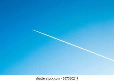 Aeroplane flying through clear blue sky with vapour trails.